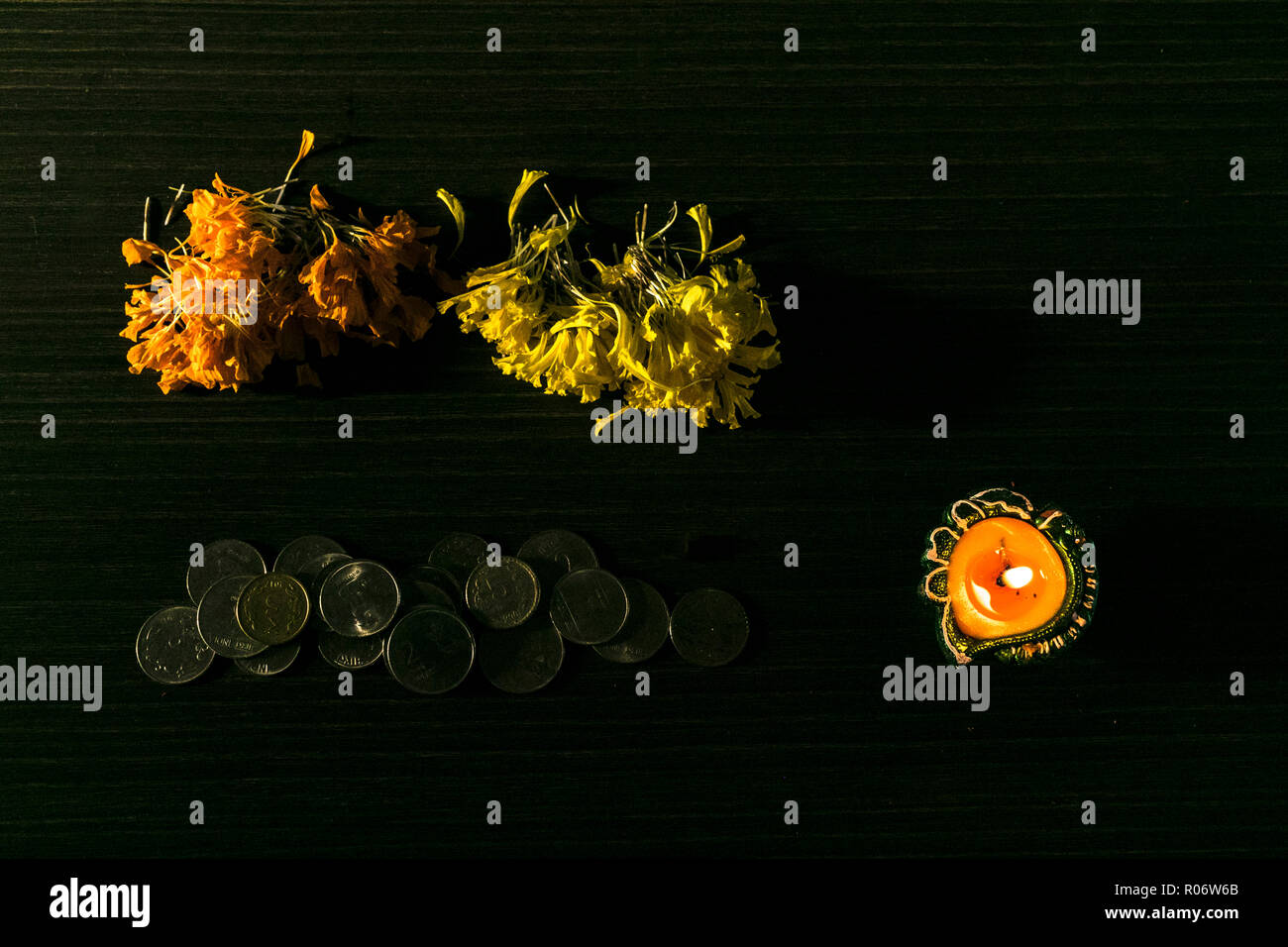 Lit diya and coins placed on black background to celebrate Diwali and Dhanteras Stock Photo