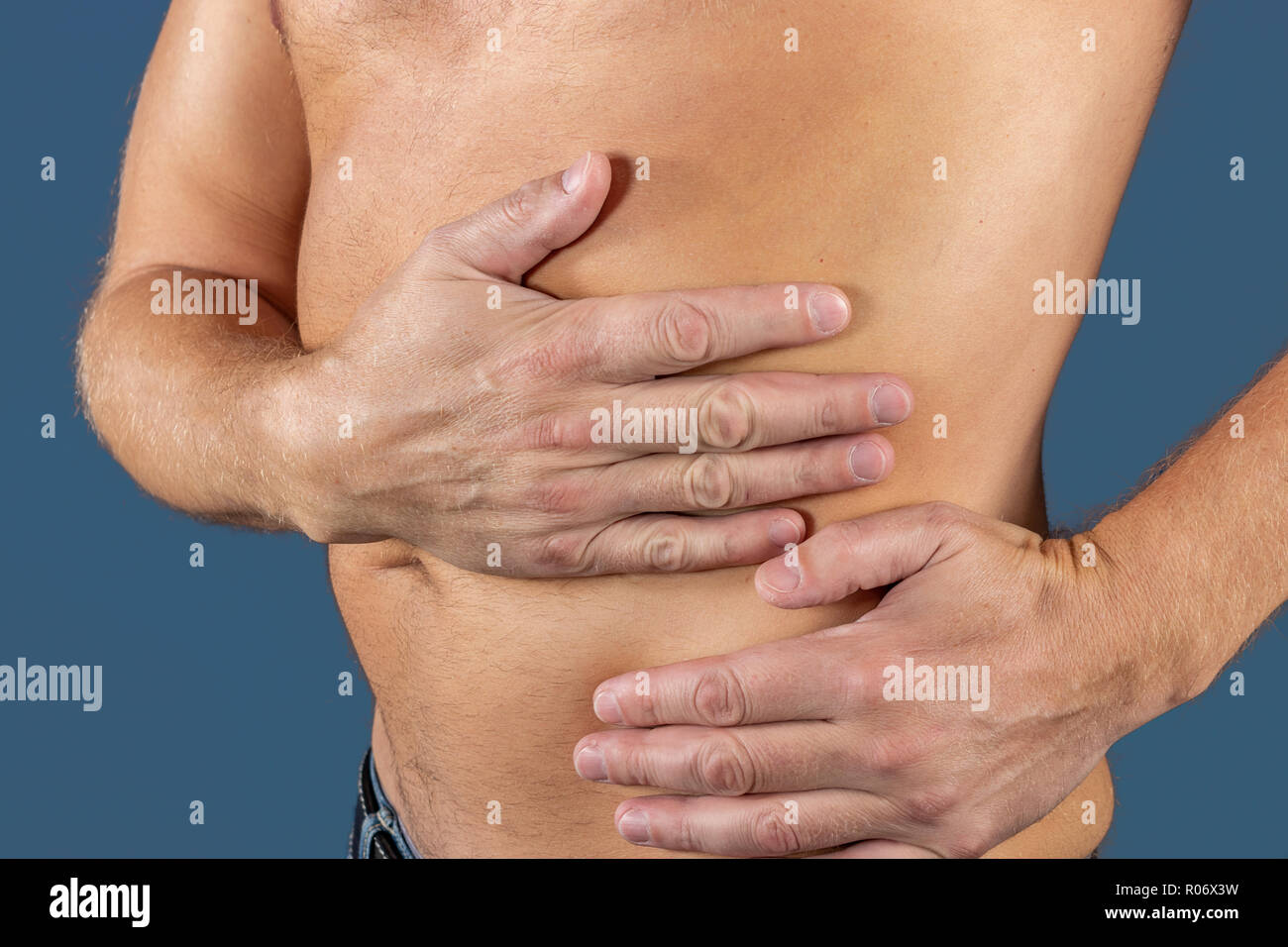 Man suffering from pain in his side. Blue background - Stock Image