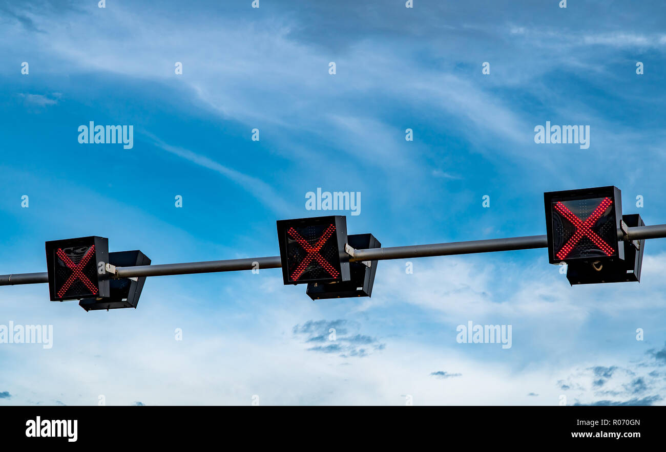 Traffic signal light with red color of cross sign on blue sky and white clouds background. Wrong sign. No entry traffic sign. Red cross guidance stop  - Stock Image
