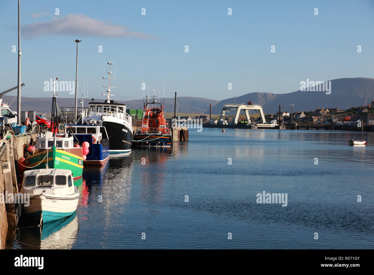 The harbour in Stromness, Orkney with fishing boats, the lifeboat and the hills of Hoy in the background - Stock Image
