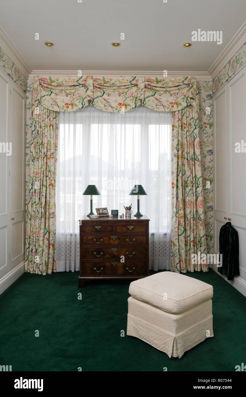 Drawers by window with floral curtains - Stock Image
