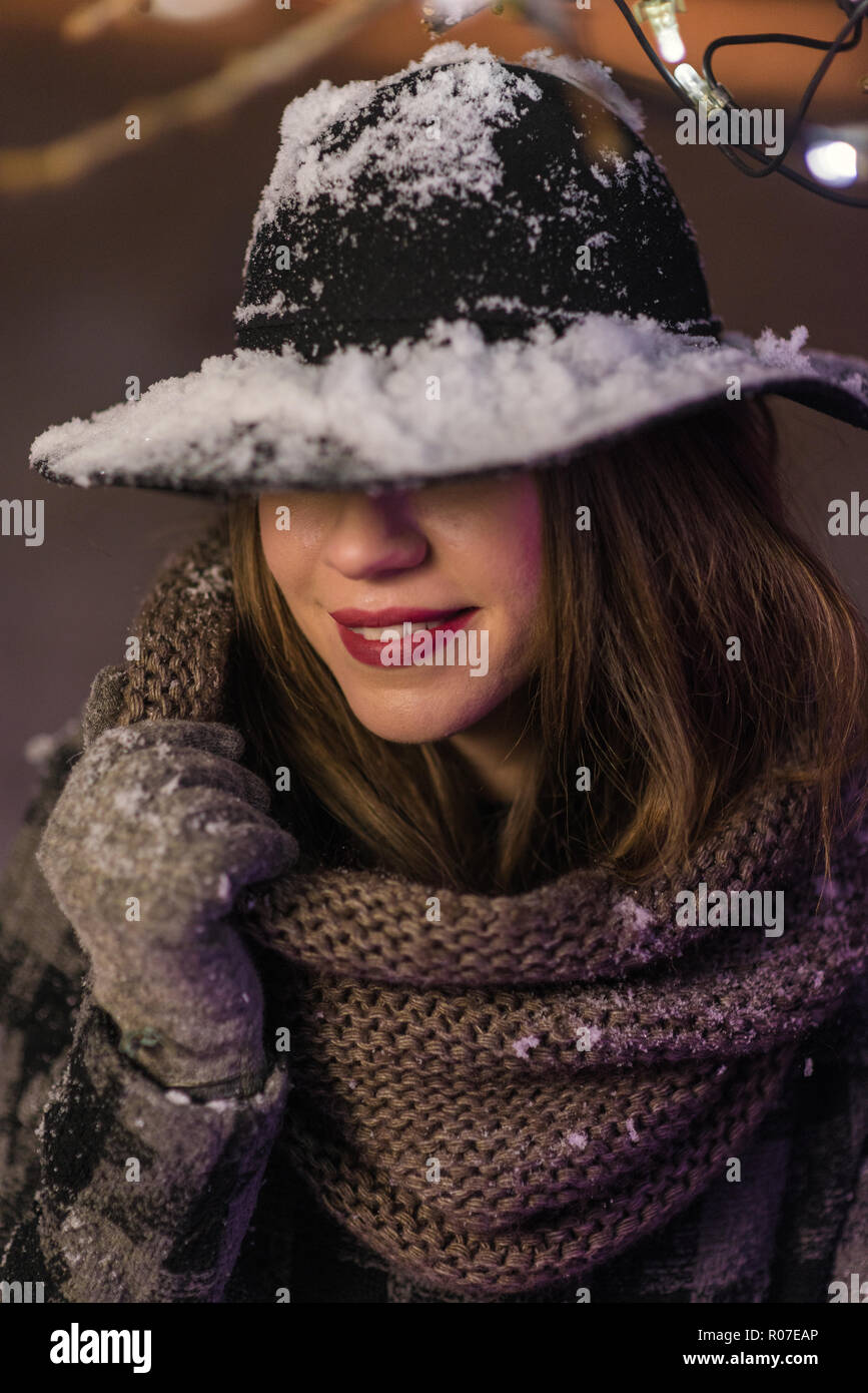 d1636508f12 Young girl with black hat with snow standing in front of Christmas tree  lights at night with snowflakes falling