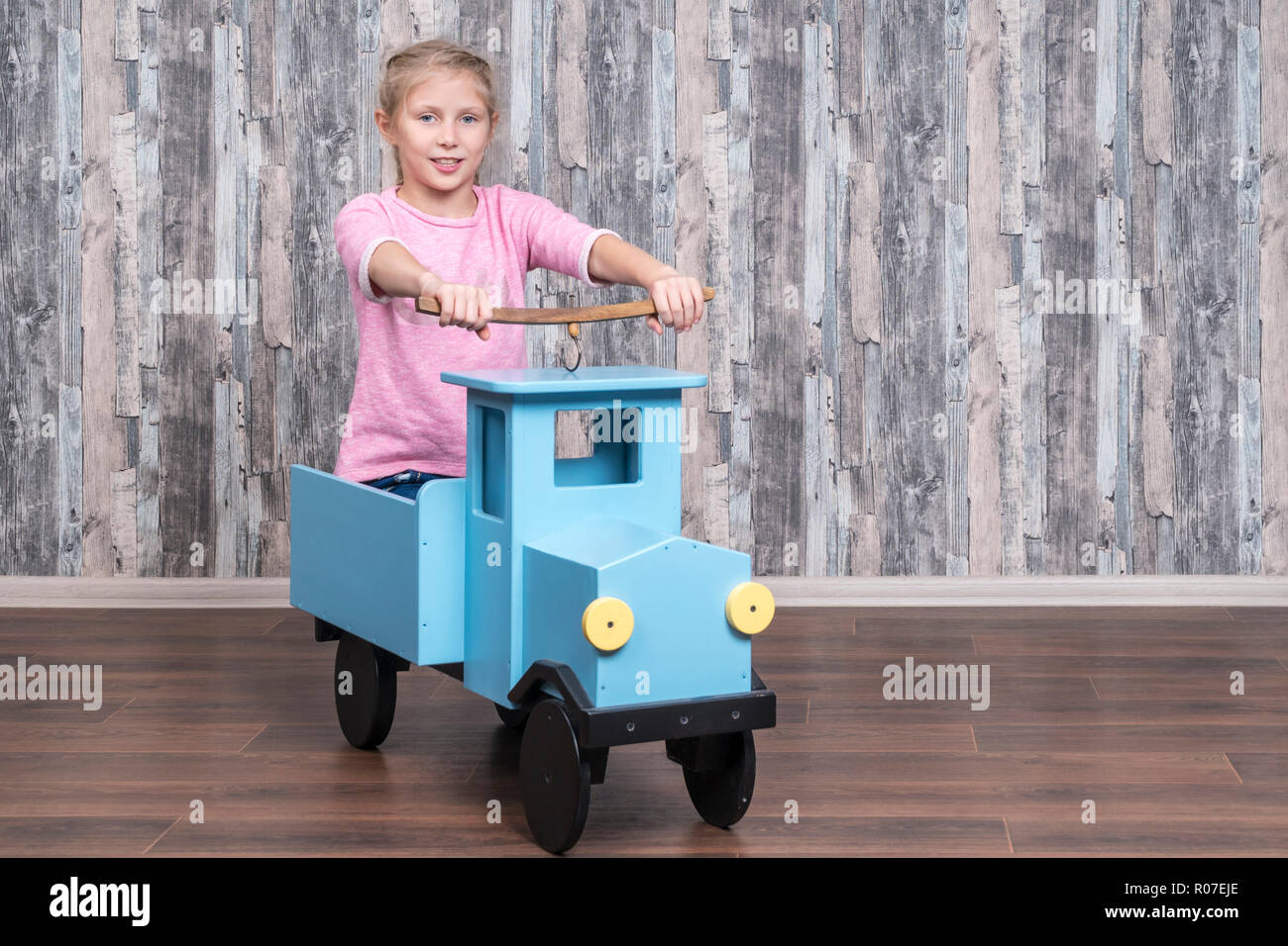 beautiful girl drives a toy wooden car while sitting in her trunk - Stock Image
