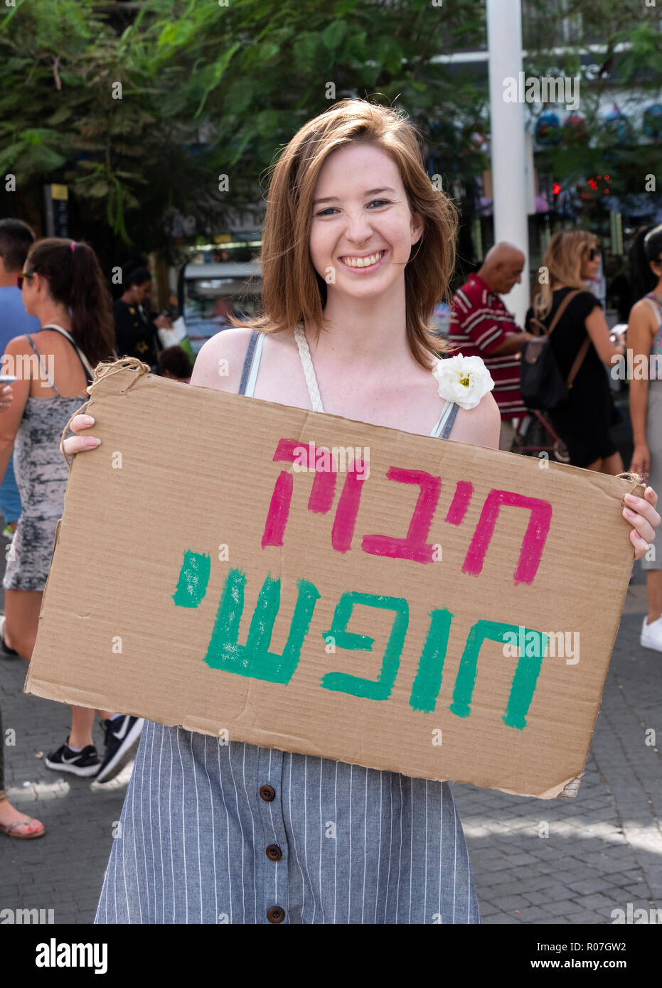A smiling young lady with a Hebrew sign saying 'Free Hug' at the Carmel Market in Tel aviv, Israel. - Stock Image
