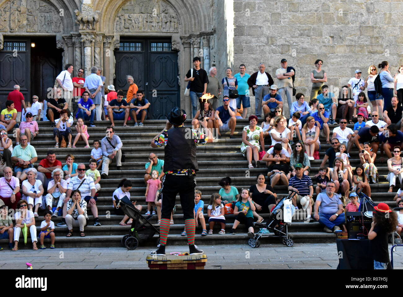 Santiago de Compostela, Spain. August 2018. A fire eater performs in front of the Cathedral. Little girl helper. Platerias Square. Stock Photo
