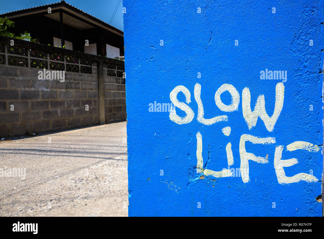 Blue painted with slow life text written on wall Stock Photo