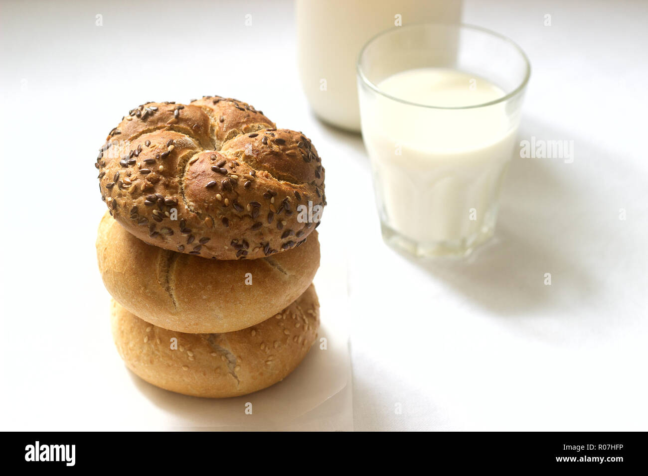 Wheat and rye Kaiser buns with flax and sesame seeds served with milk, healthy breakfast. Stock Photo