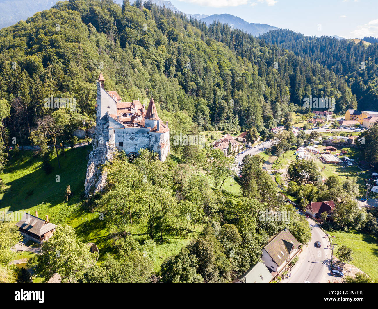 Bran castle on a hill with high spires, walls, red tiled roofs, surrounded by Bran town, Wallachia, Transylvania, Romania. Known as Dracula's Castle. - Stock Image