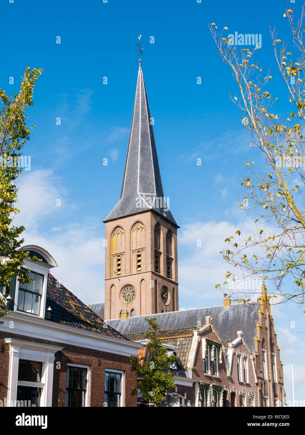 Tower of Saint Werenfridus Church and top facades of traditional houses in historic old town of Workum, Friesland, Netherlands Stock Photo
