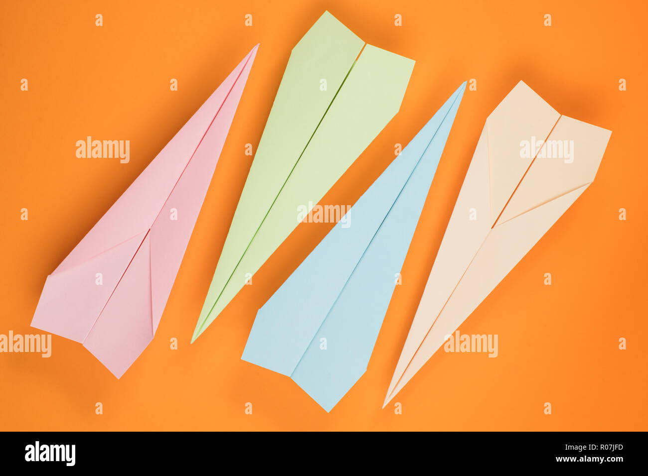 Colored paper planes on orange paper background. Top view - Stock Image