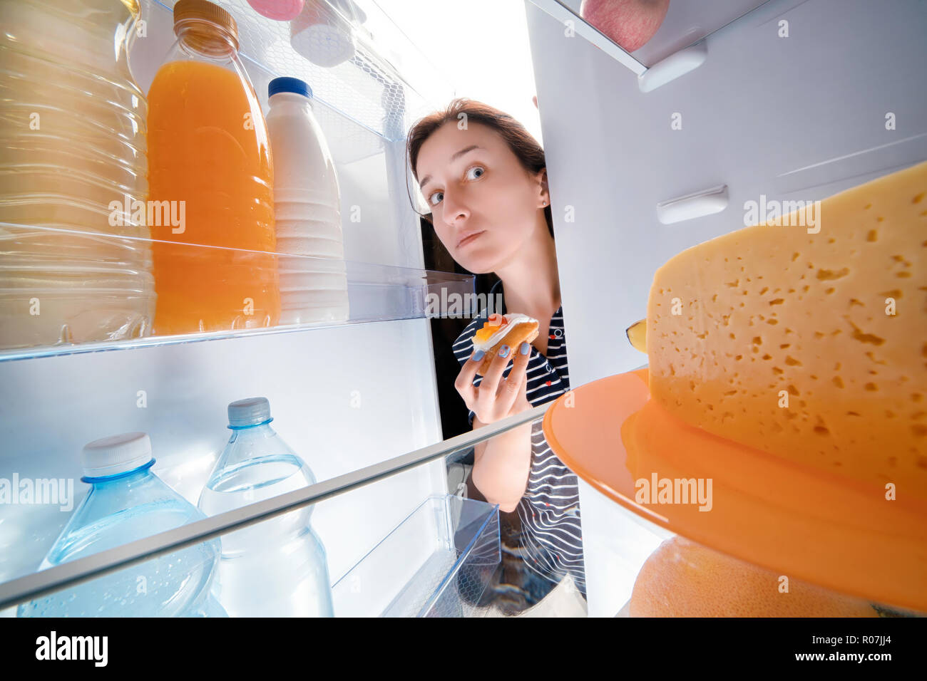 Tricky girl holding sweet cake and looking into fridge full of different food. Wide angle view from inside - Stock Image