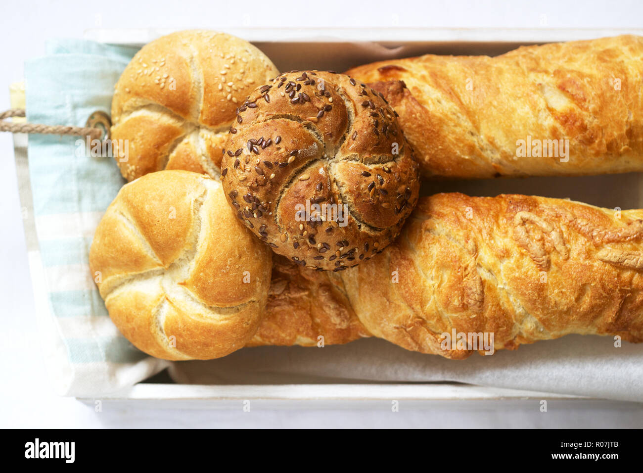 Kaiser wheat and rye flour buns with seeds, mini baguettes with ham and cheese, fresh bread. Stock Photo