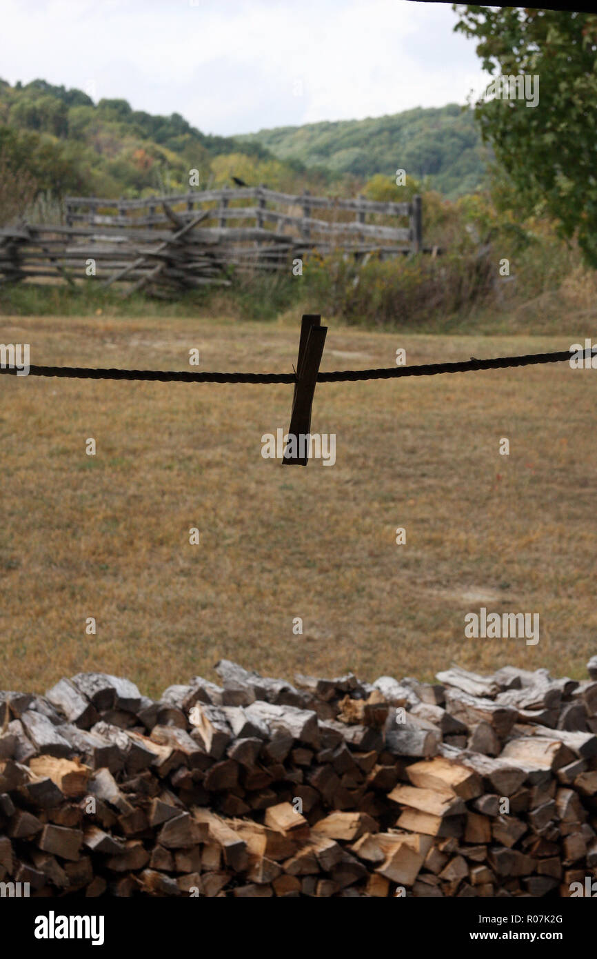 Old-style farm life, with clothespin on laundry line and stacked firewood. Frontier Culture Museum, VA Stock Photo