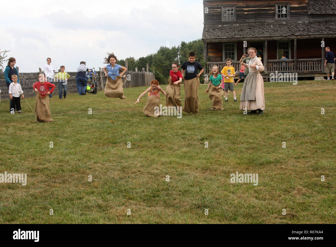 Children competing in a potato sack race at the Frontier Culture Museum in Staunton, VA - Stock Image