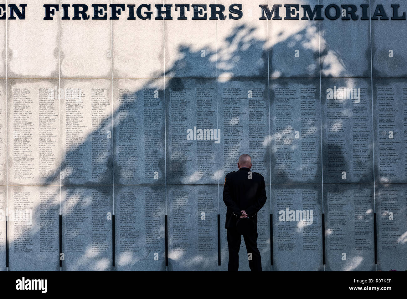 Firefighter reflects on lost collegues at the New York Firefighters Memorial, Albamy, New York, USA. - Stock Image