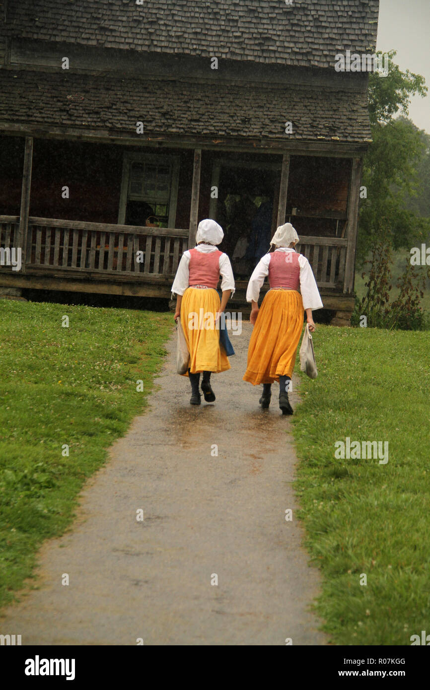 Young girls reeanctors walking through rain at Frontier Culture Museum in Staunton, VA. 19th century-style clothing. - Stock Image
