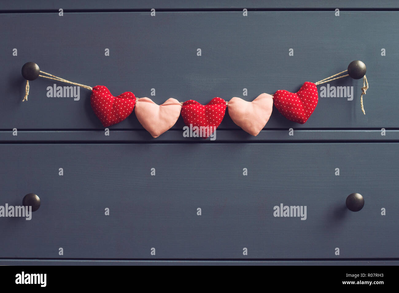 horizontal front view detail of blue vintage wooden chest of drawers with red dotted plush hearts on a string in a nursery room of apartment or house  - Stock Image