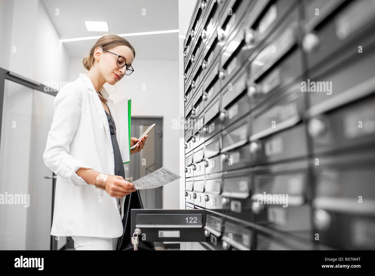Dispirited woman checking bills getting correspondence from the mailboxes in the walk hall of the residential building - Stock Image