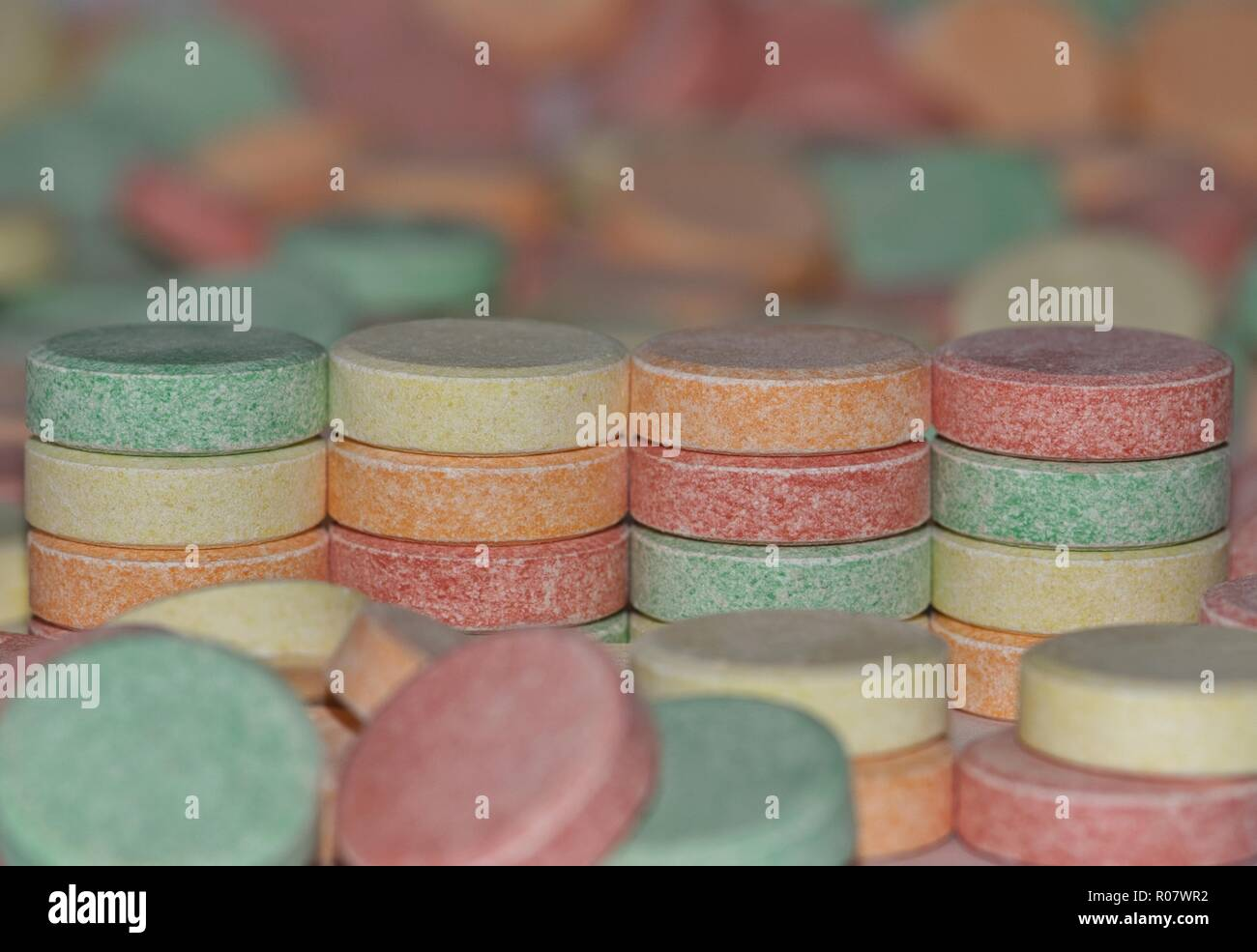 A colorful image showing four stacks of common antacid pills with many other scattered pills in the foreground and background. - Stock Image