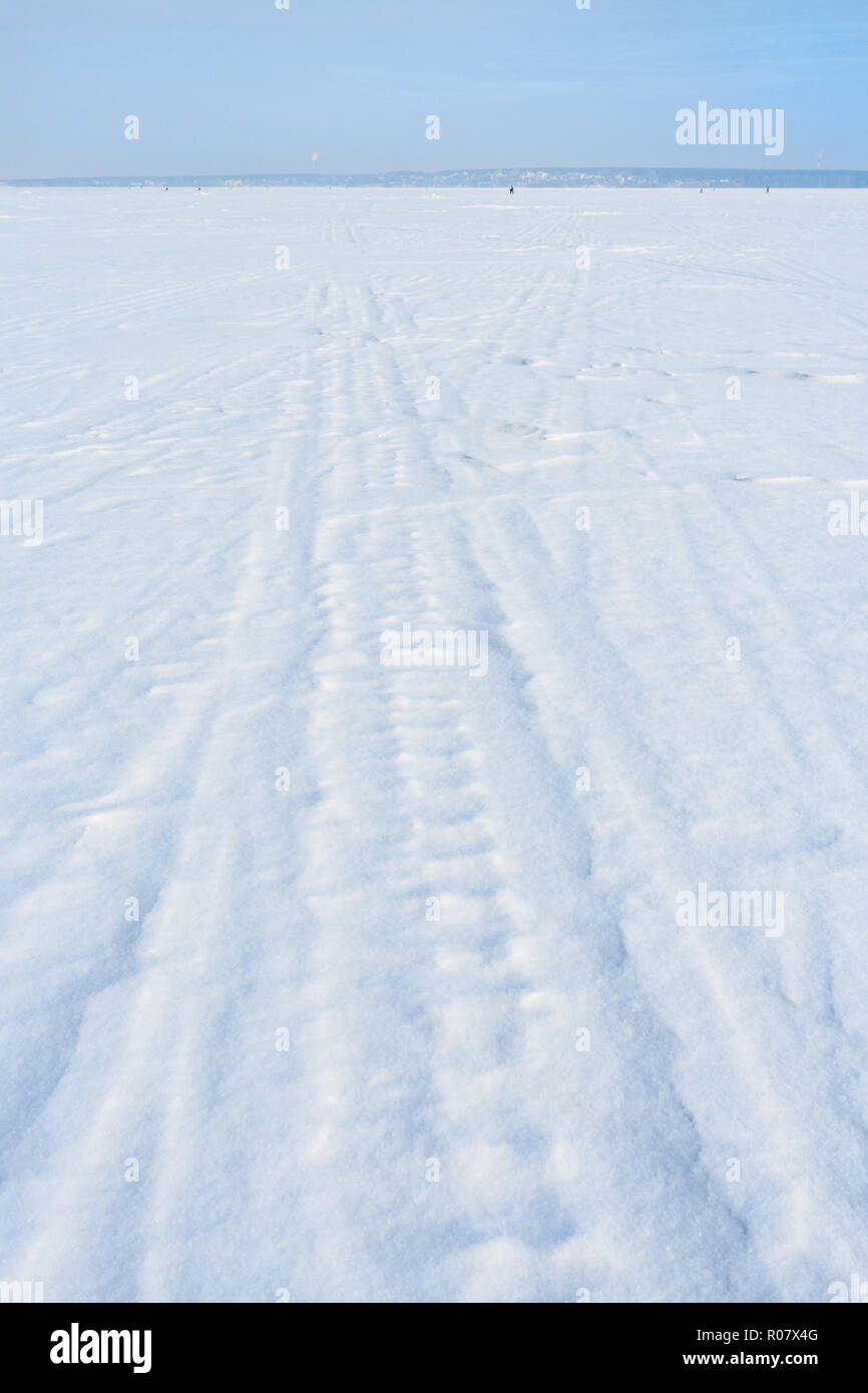 Traces of sledge runners and ski on white freshly fallen snow on winter frozen lake. - Stock Image