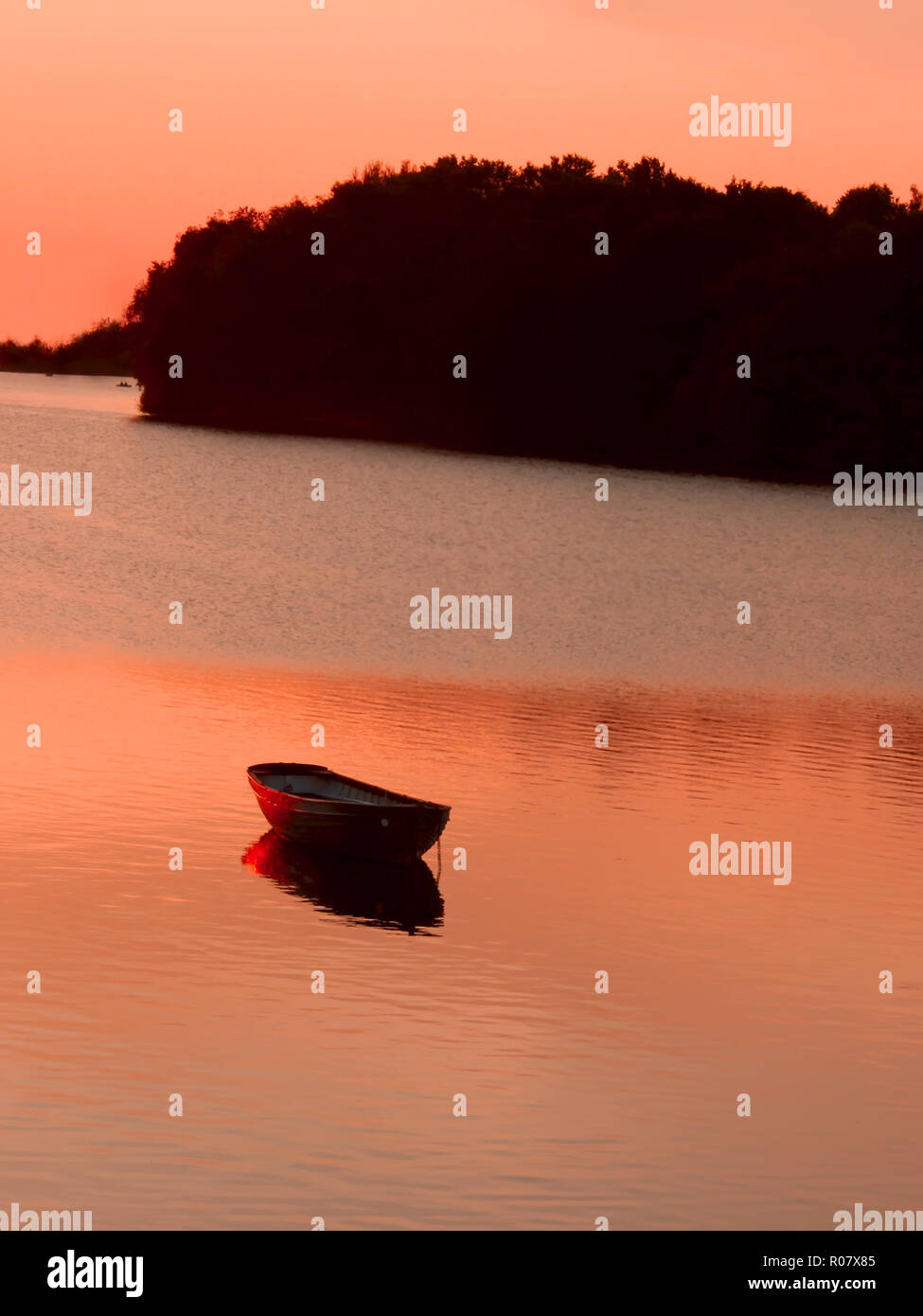 Anchored boat in the reservoir after sunset in quiet summer weather. Khmelnitsky, Ukraine - Stock Image