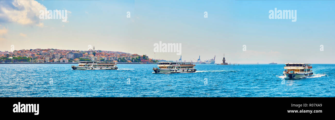 Ferryboats crossing the Bosphorus, with the Eminonu neighborhood skyline and The Maiden's Tower in the background. Istanbul, Turkey. - Stock Image