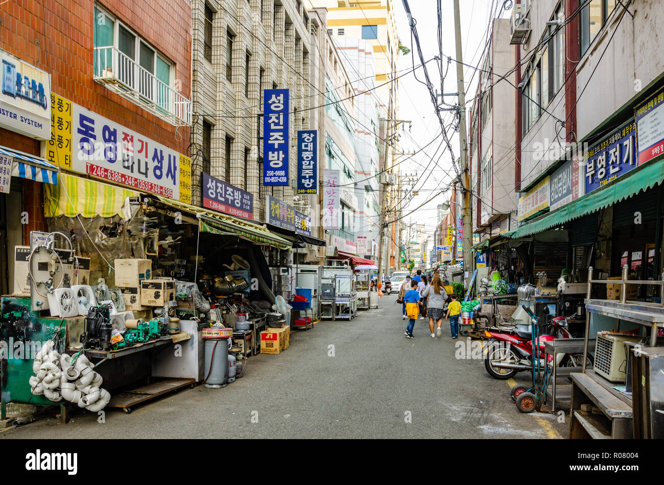 Overhead power cables criss-cross a street lined with hardware stores in Busan, South Korea. - Stock Image