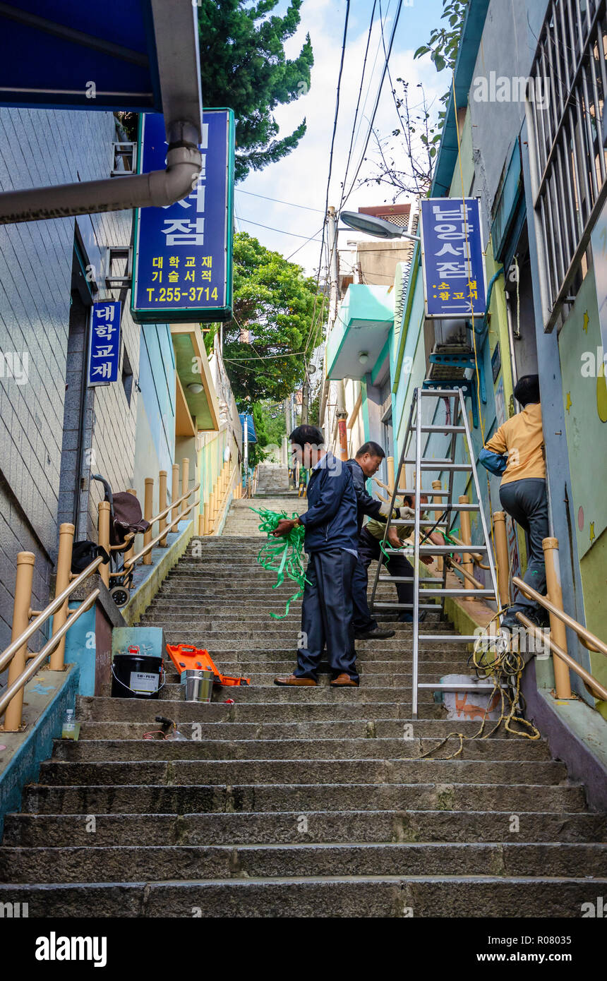 Workmen balance a step ladder on a long flight of stairs to do some maintenance work on a property in Busan, South Korea. - Stock Image