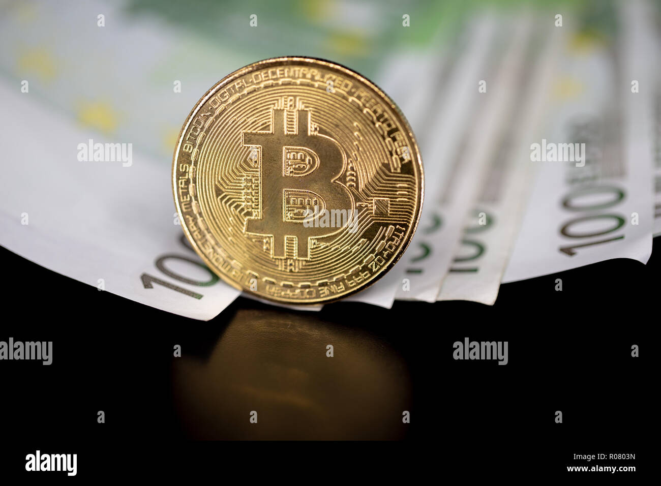 Bitcoin token on black with reflection, with a big pile of euro banknote money in the background Stock Photo