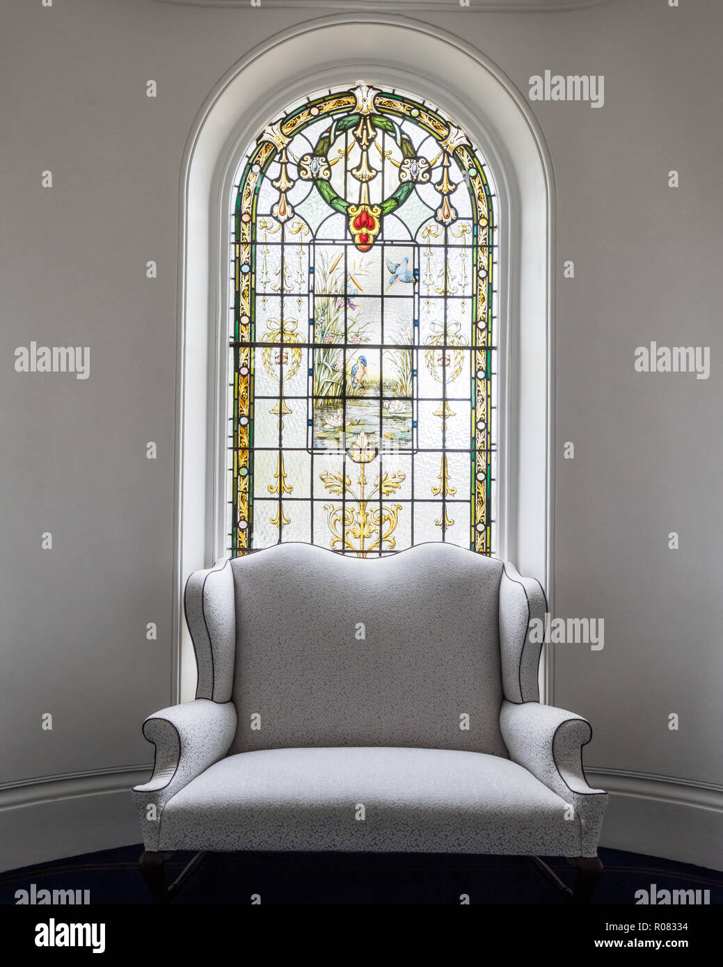 Armchair by stained glass window - Stock Image