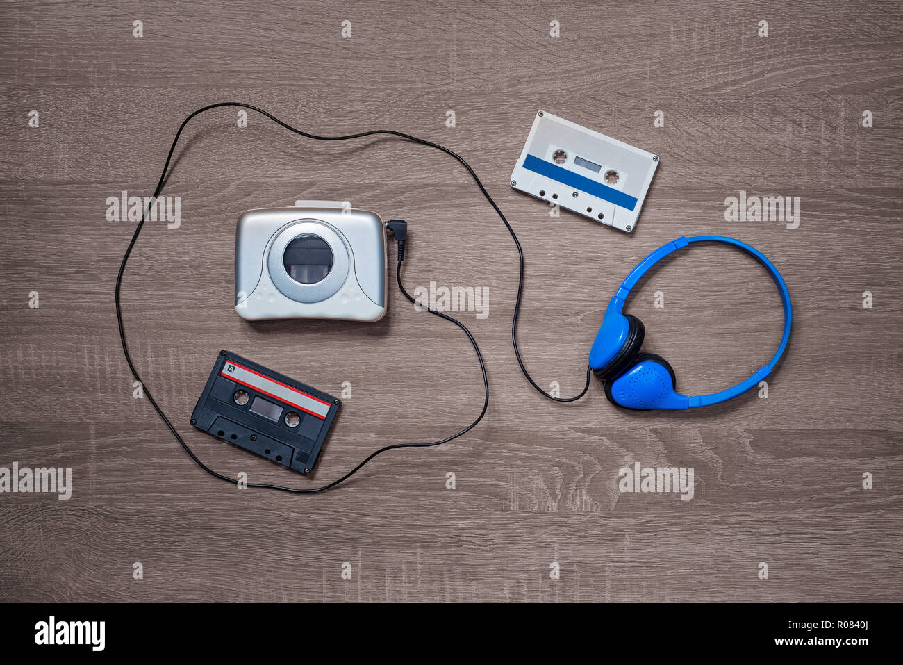 Vintage walkman, cassette and headphones on the wooden background - Stock Image