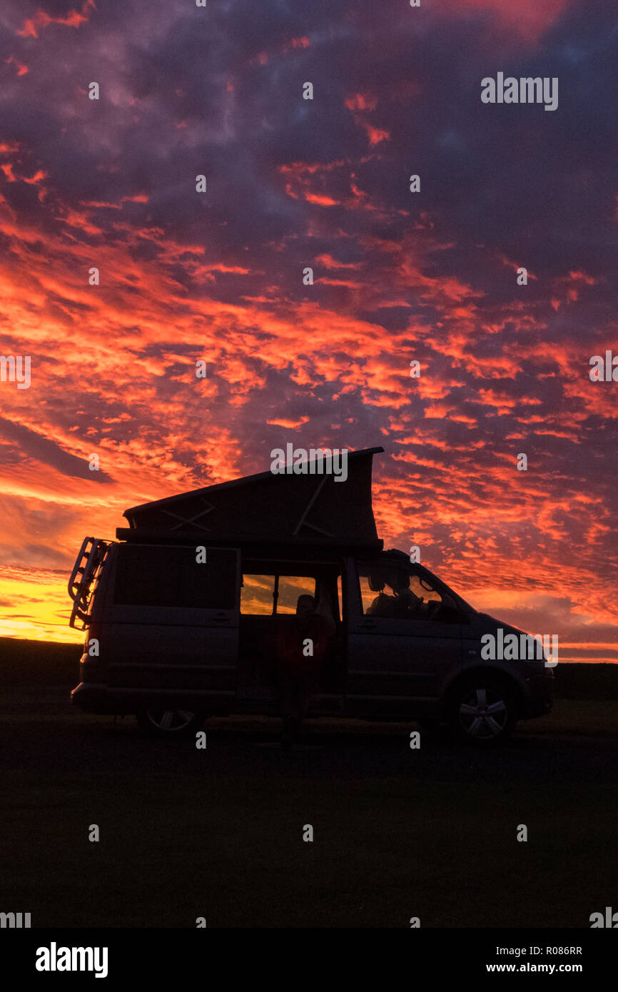 vw camper van silhouetted against brilliant red sunset, Crail, Fife, Scotland, UK - Stock Image