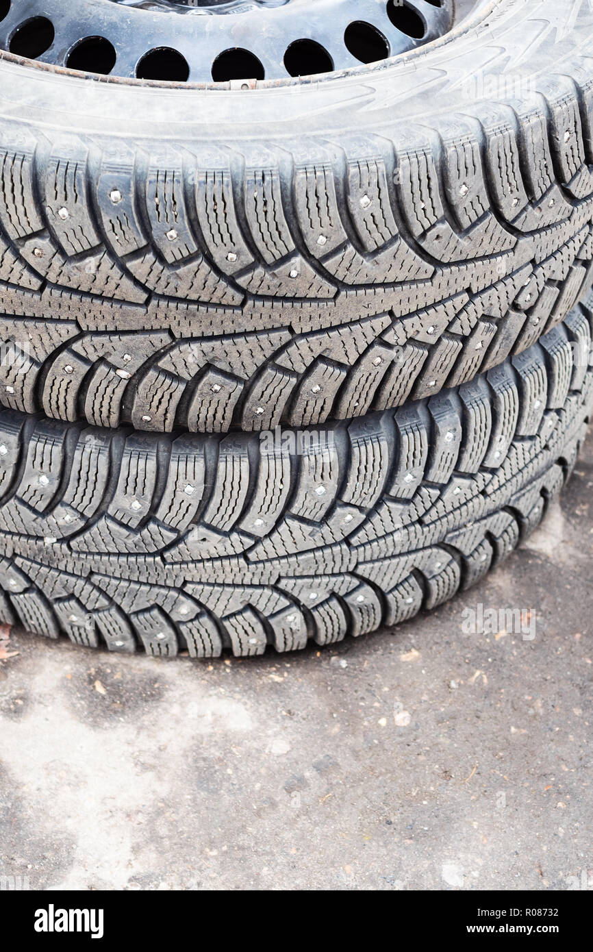 pair of old studded snow tires on ground during for seasonal replacement of wheels - Stock Image