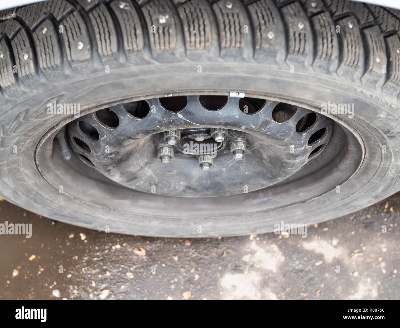 top view of attached used studded winter tire on car during for seasonal replacement of wheels - Stock Image