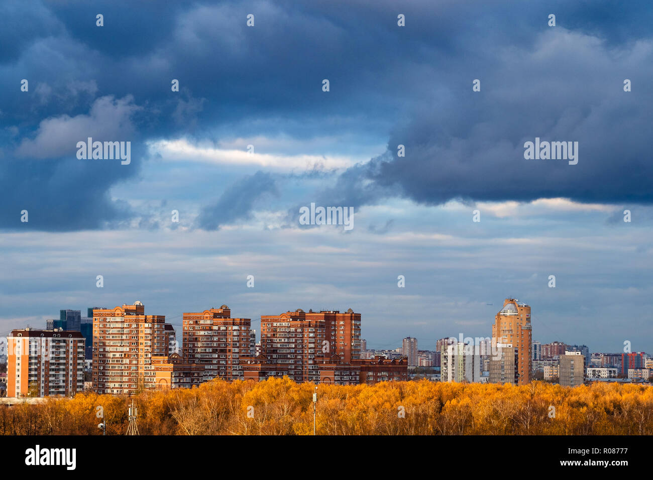 dark blue snow storm clouds over apartment houses in city in autumn - Stock  Image