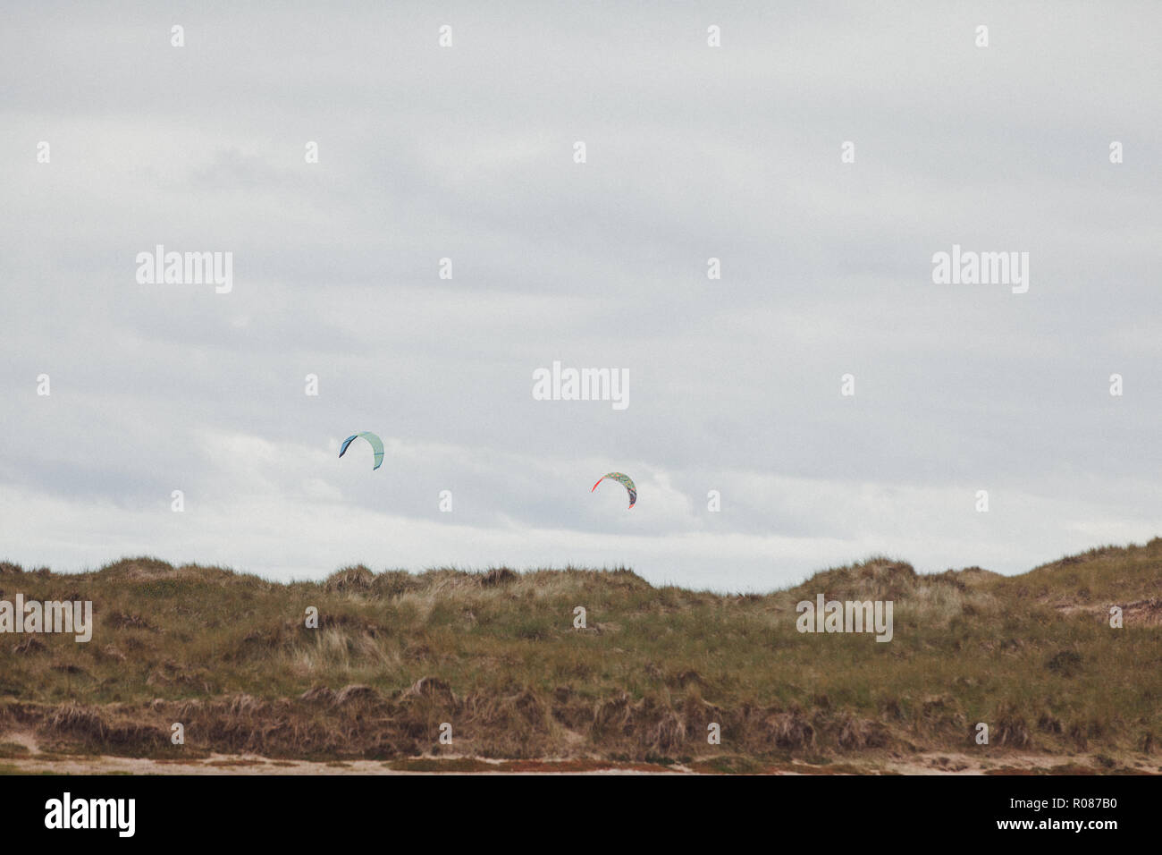 kites of kite surfers visible above the skyline of the sand dunes at Rhosneigr, Anglesey, North Wales, UK - Stock Image