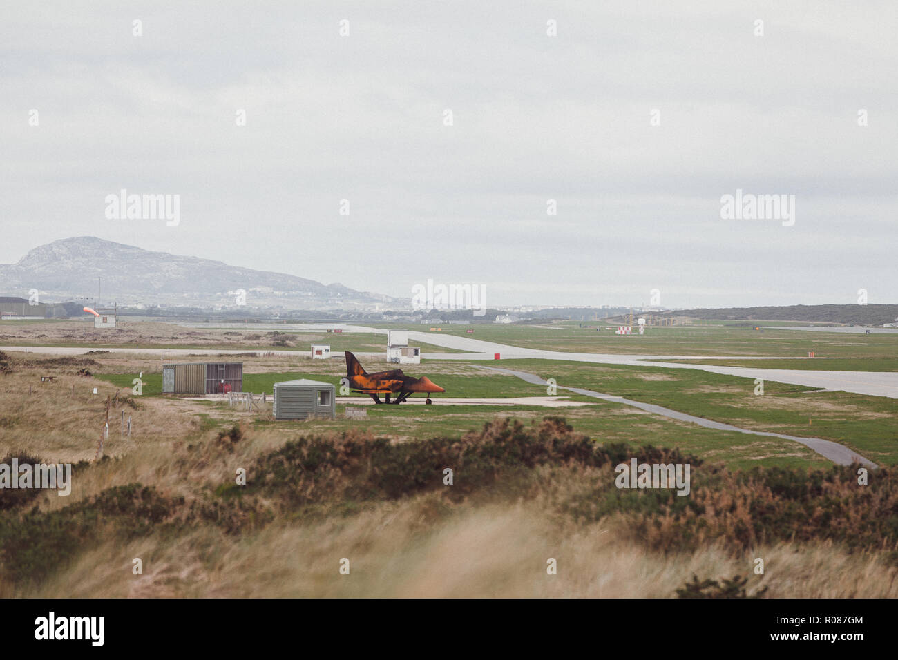 disused jet plane, on Valley runway, Rhosneigr, Anglesey, North Wales, UK, with Holy Mountain, Holy Island, in the background - Stock Image