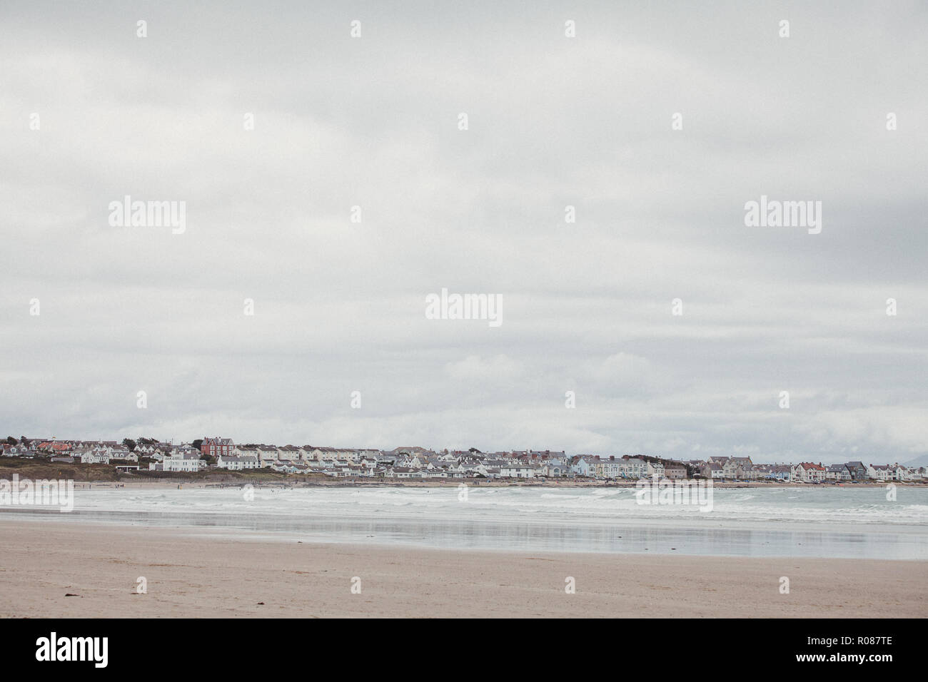 Looking across Cymyran beach towards Rhosneigr town, Anglesey, North wales, UK - Stock Image