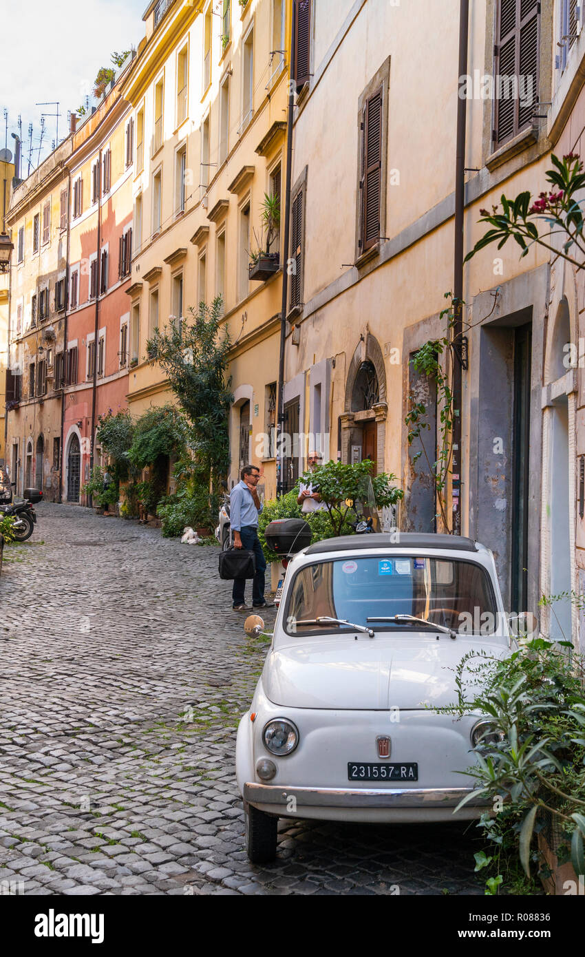 Old Fiat 500 car and colourful old houses in the Trastevere district of Rome, central Italy. - Stock Image