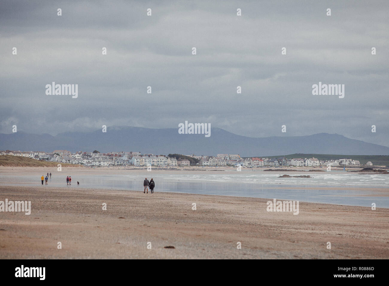 People walking along Cymyran beach, Rhosneigr, Anglesey, North Wales, UK, the Snowdonia Mountain Range in the background - Stock Image