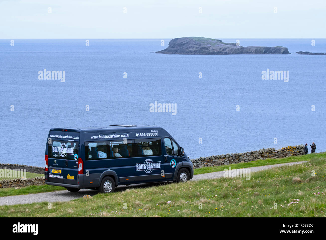 Group tourists driving along desolate coastal road in rented van / hired van from the Bolts Car Hire company in Shetland, Scotland, UK - Stock Image