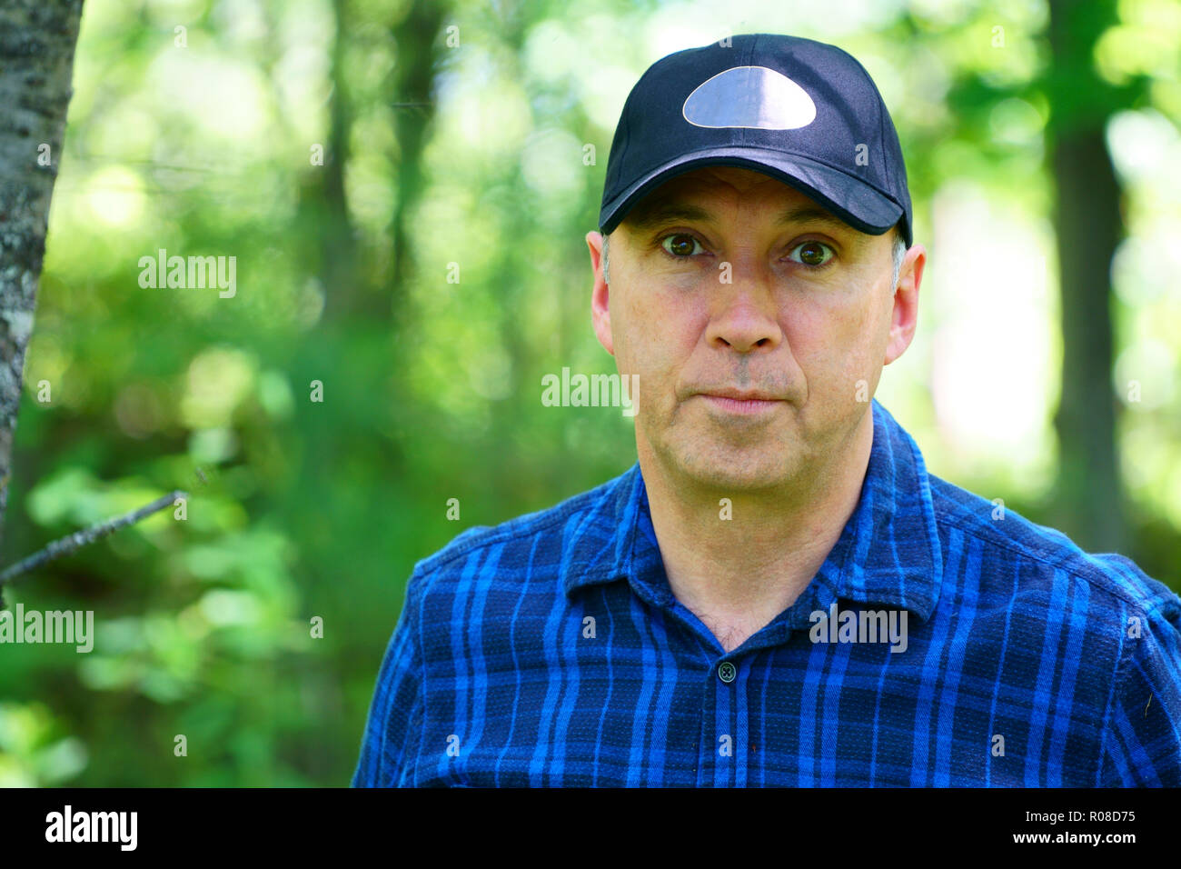 A caucasian serious man is looking into the camera for a portrait while hiking in the forest wearing a blue check shirt and a black hat. - Stock Image