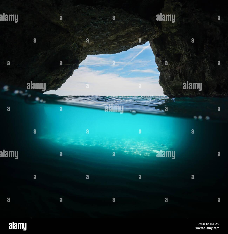 Inside a cave on seashore with sand underwater, split view half above and below surface, Mediterranean sea, Spain, Costa Dorada, Cova Del Llop Mari - Stock Image