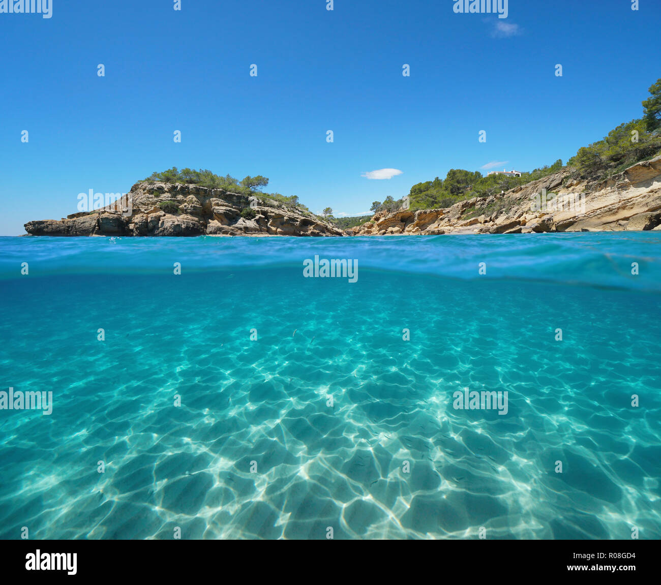 Rocky coast with an islet and sand underwater, split view half above and below water surface, Mediterranean sea, l'Illot, L'Ametlla de Mar, Spain - Stock Image