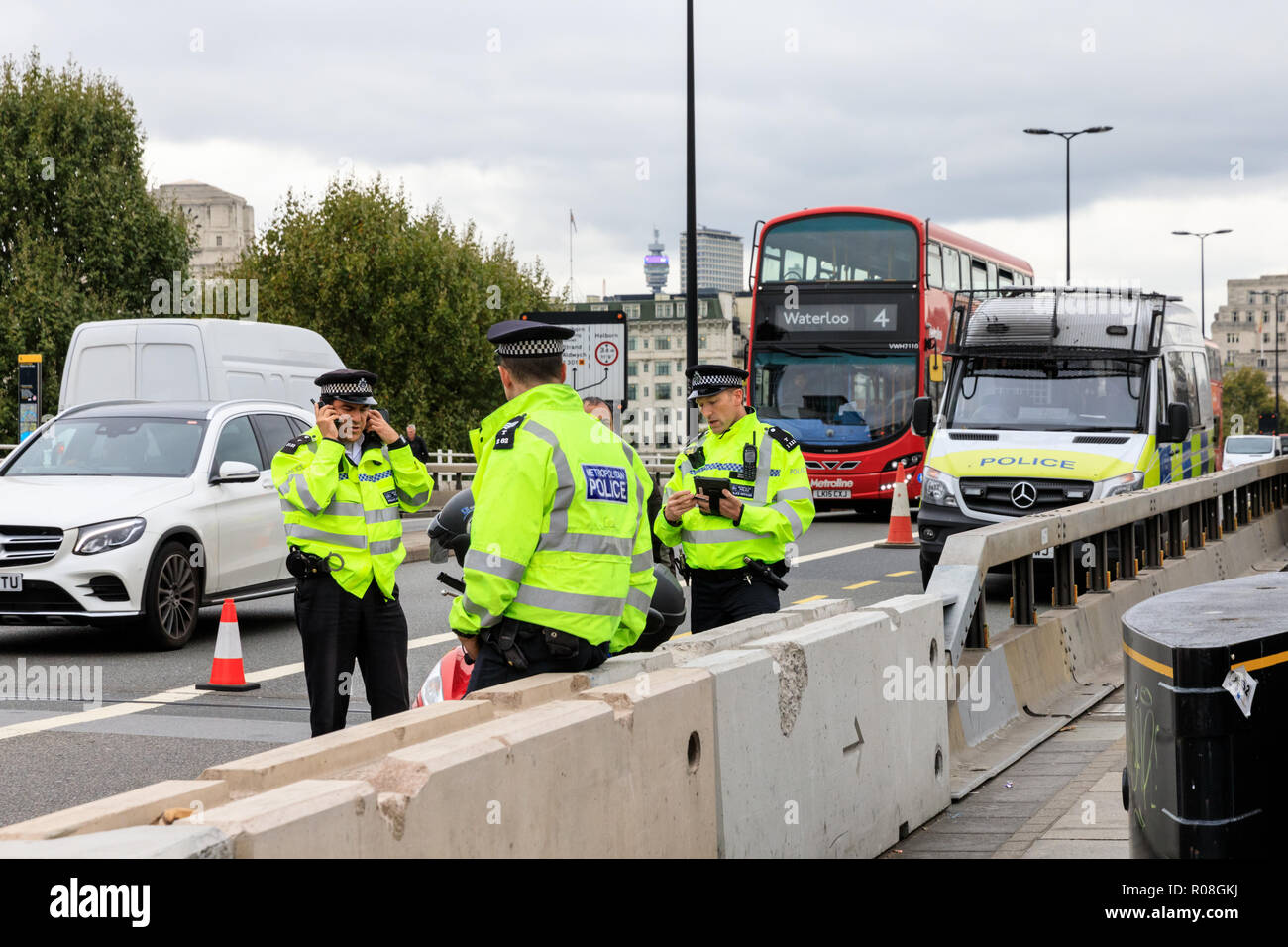 Metropolitain Police officer stop cars and speak to drivers during a stop and search security measure in Waterloo Bridge, London - Stock Image