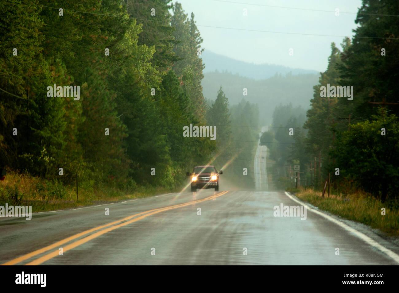 Truck driving on rain slicked road near Flathead Lake, Montana Stock Photo