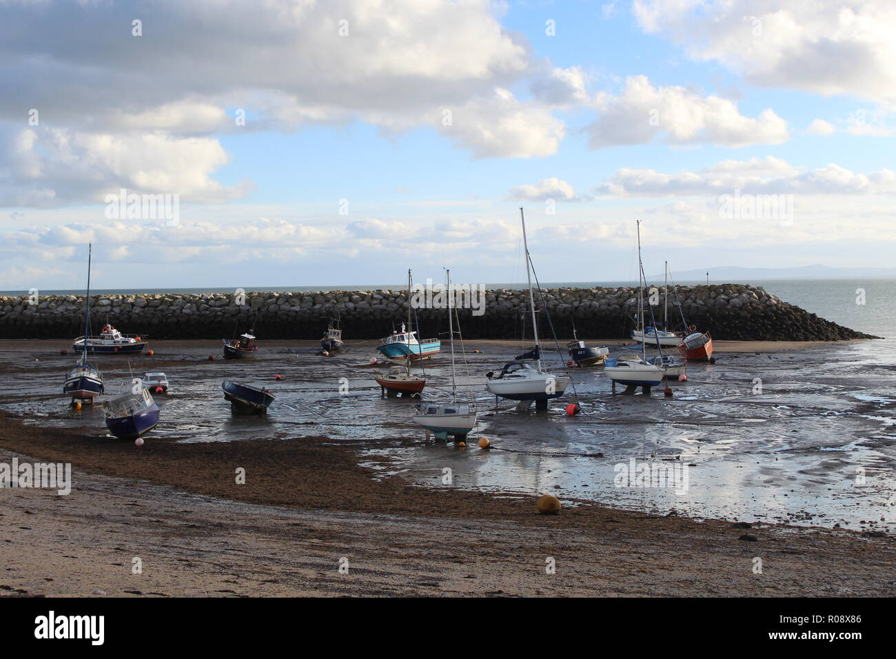 Boats washed up on the beach in Rhos-on-sea, Wales. - Stock Image