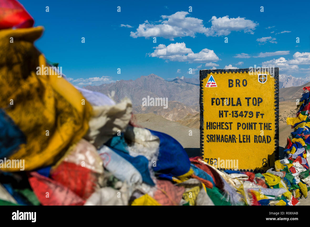 The milestone at Fotu La top, a pass at an altitude of 4.108 m above sea level on Srinagar-Leh-Highway, surrounded by buddhist prayerflags - Stock Image