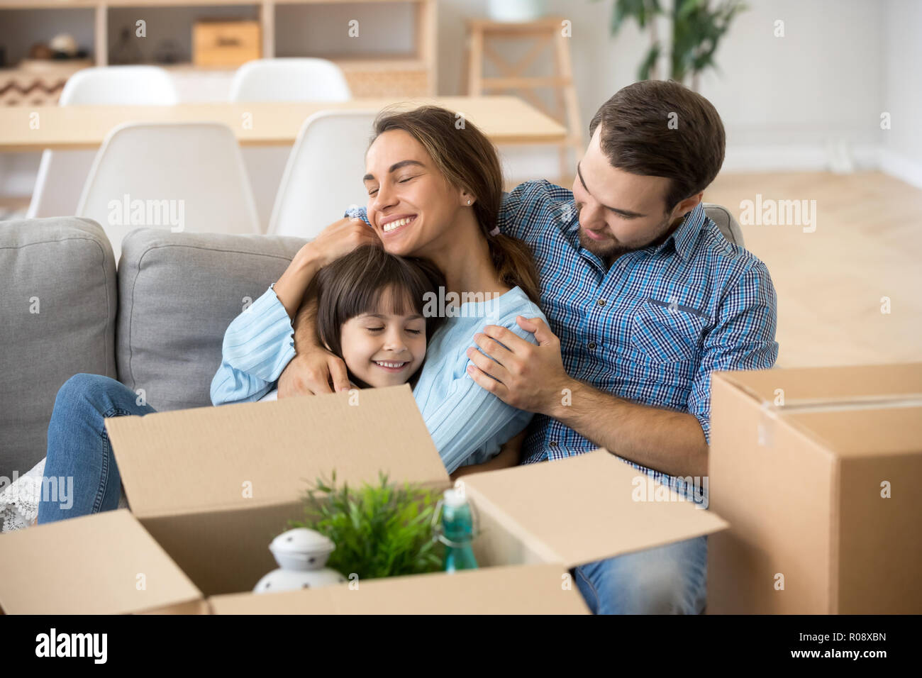 Happy family spending time at new wealthy modern home - Stock Image