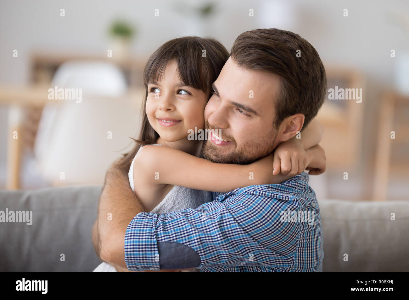 Father and daughter embracing sitting on couch looking at camera Stock Photo